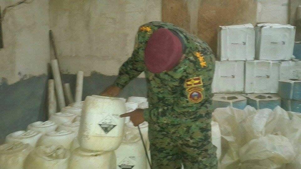 Un des officiers irakiens montre du doigt des bidons avec des substances dangereuses pour l'homme