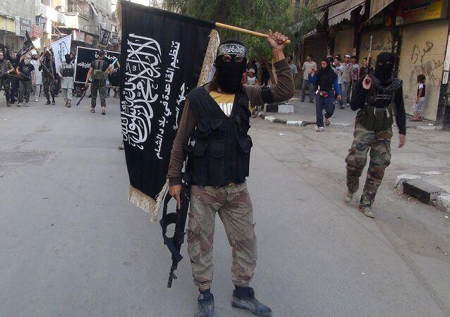 Des combattants du Front-al-Nosra brandissent leur drapeau en défilant dans un camp de réfugiés palestiniens au sud de Damas