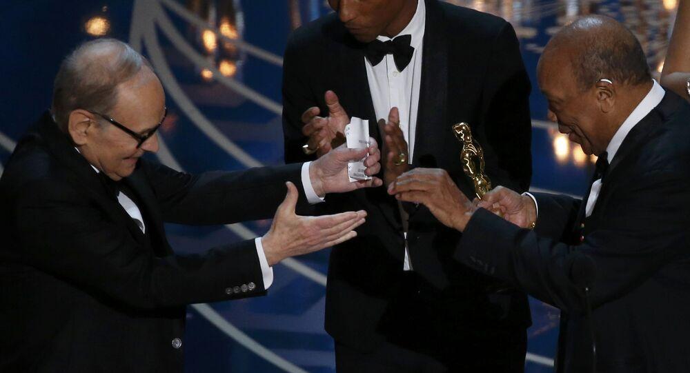 Le compositeur Ennio Morricone (L) reçoit l'Oscar pour la meilleure musique du film Les Huit Salopards
