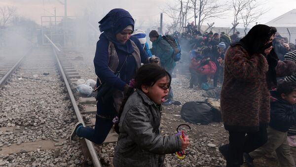 Migrants and refugees run away from tear-gas and stun grenades after Macedonian police fired tear gas at hundreds of Iraqi and Syrian migrants who tried to break through the Greek border fence in Idomeni, on February 29, 2016. - Sputnik France