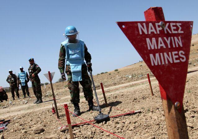 Un expert de la mine FINUL cambodgienne démontre son travail le 23 Avril, 2014 dans la zone contrôlée par l'ONU, où les opérations de déminage sont menées sous les auspices de la Force de maintien de la paix des Nations Unies à Chypre (UNFICYP), près du village de Mammari