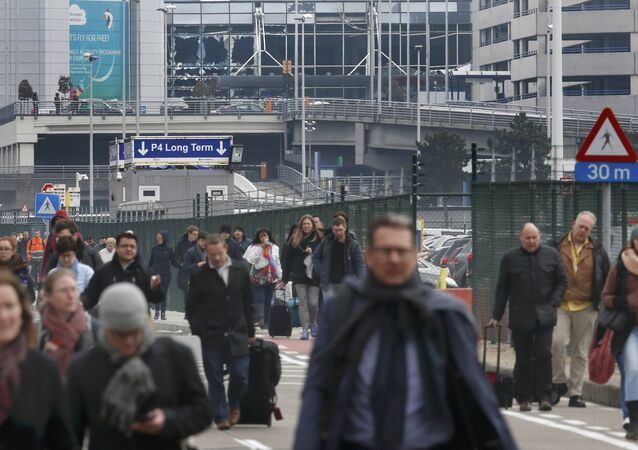 Les gens quittent la scène des explosions à l'aéroport de Zaventem
