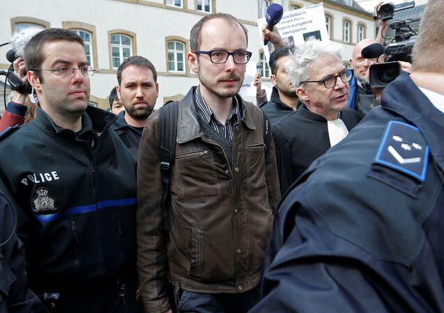 Antoine Deltour escorté par les membres de la police, le 26 avril