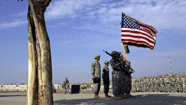 US soldiers carry an American flag as they unfurl their division's new colors during a handover ceremony from the 4th Infantry Division to the 1st Cavalry Division at a US military base in Baghdad, 15 November 2006. - Sputnik France