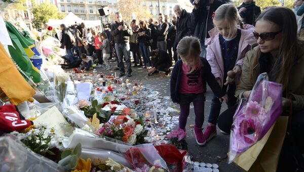 People place flowers and candles along a police cordon set-up close to the Bataclan concert hall on November 15, 2015 in Paris, following a series of coordinated attacks in and around Paris on November 13. - Sputnik France