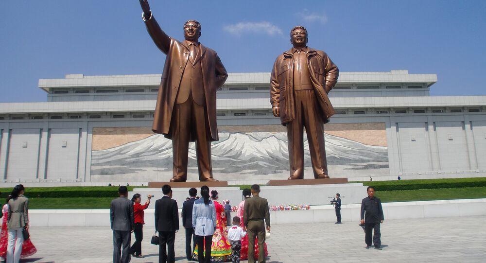 Des jeunes mariés et leurs proches devant le Grand Monument Mansudae à Pyongyang