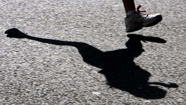 A runner's shadow is cast onto the road as she enters the last five miles of the challenging route, 22 April 2007. - Sputnik France