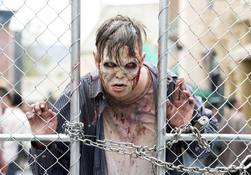 Un homme déguisé en zombie dans une zone thématique dédiée à la série télévisée Walking Dead dans le parc d'attractions Universal Studios Hollywood