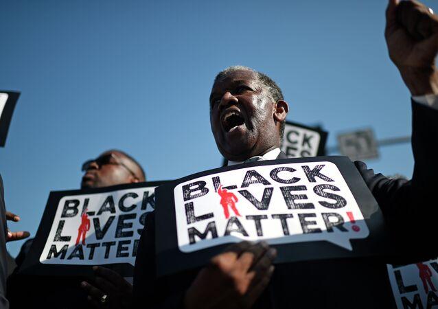 Une homme porte une pancarte Black Lives Matter lors d'une marche en l'honneur de Martin Luther King Jr.