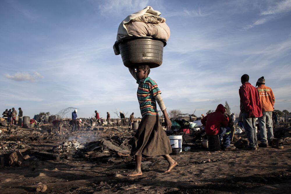Une femme porte sur sa tête tout ce qu'il lui reste après un incendie à Pretoria en Afrique du Sud.