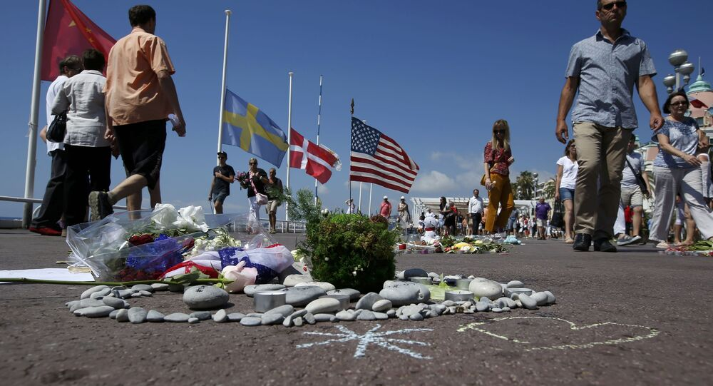 People walk past a heart shape makeshift memorial with a U.S. flag placed on the road in tribute to victims before a minute of silence on the third day of national mourning in France. Nice, July 18, 2016