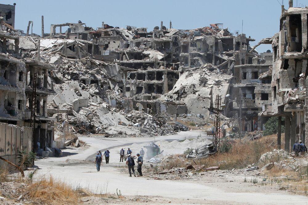 Des ouvriers dans les décombres de Homs en Syrie