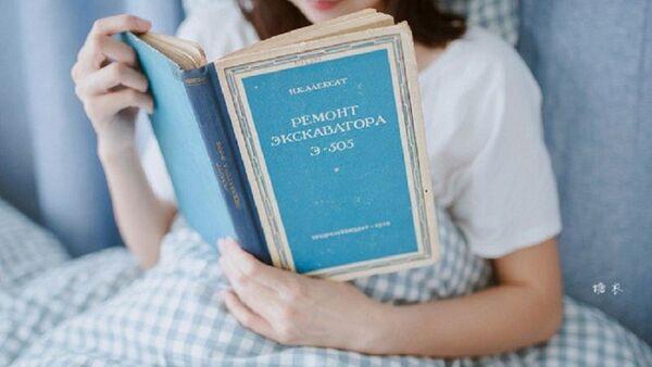 une jeune fille chinoise lisant un livre en russe intitulé Réparation de la pelleteuse E-505 - Sputnik France
