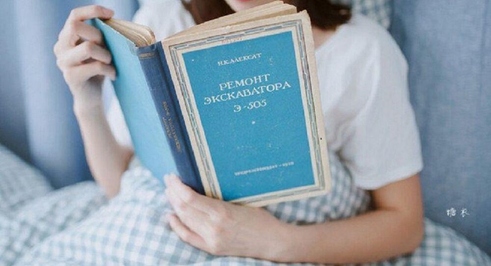une jeune fille chinoise lisant un livre en russe intitulé Réparation de la pelleteuse E-505