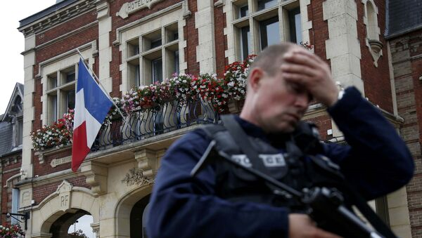 A policeman reacts as he secures a position in front of the city hall after two assailants had taken five people hostage in the church at Saint-Etienne-du -Rouvray near Rouen in Normandy, France, July 26, 2016. - Sputnik France