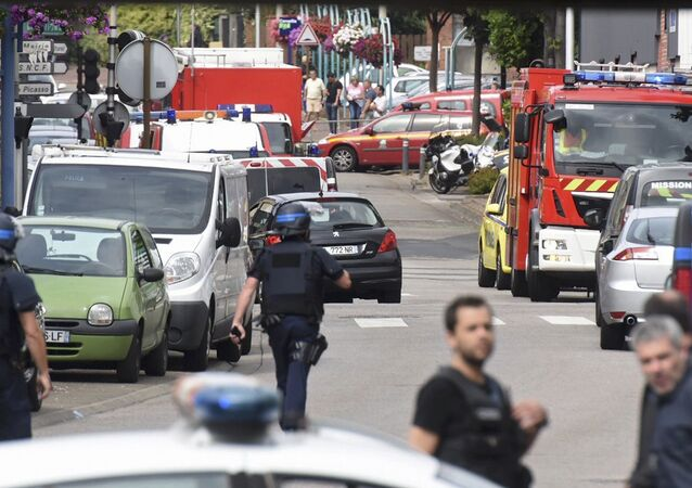 Police and rescue workers stand at the scene after two assailants had taken five people hostage in the church at Saint-Etienne-du -Rouvray near Rouen in Normandy, France, July 26, 2016.