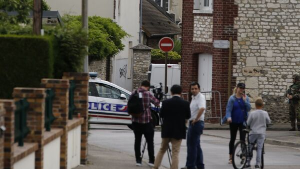 This photo taken on July 26, 2016 shows behind the church ofSaint-Etienne-du-Rouvray, blocked by police following an attack by two knife-wielding men. French President Francois Hollande that two men who attacked a church and slit the throat of a priest had claimed to be from Daesh, using the Arabic name for the Islamic State group. - Sputnik France