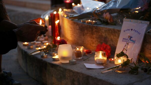 A woman lights a candle to place with flowers and candles at the town hall in Saint-Etienne-du-Rouvray, near Rouen in Normandy, France, to pay tribute to French priest, Father Jacques Hamel, who was killed with a knife and another hostage seriously wounded in an attack on a church that was carried out by assailants linked to Islamic State, July 26, 2016. - Sputnik France