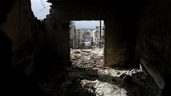 Damaged buildings are seen through a door at al-Ezaa frontline in Aleppo, March 2, 2015. - Sputnik France