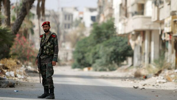 A Syrian army soldier stands at the entrance of the besieged Damascus suburb of Daraya, before the start of evacuation of residents and insurgents of Daraya, Syria August 26, 2016. REUTERS/Omar Sanadiki - Sputnik France