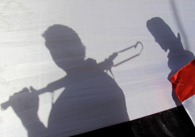 Les ombres de rebelles Houthis portant un drapeau yéménite