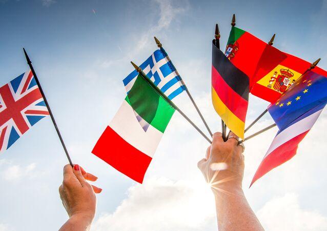 Une personne tient des drapeaux des pays européens dans une main et un drapeau Royaume-Uni dans une autre