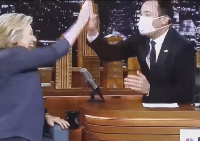 Il enfile un masque médical… pour accueillir Hillary Clinton (Vidéo)