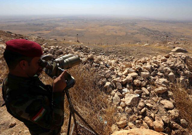 An Iraqi Kurdish Peshmerga fighter looks through binoculars on the top of Mount Zardak, about 25 kilometres east of Mosul, on October 6, 2016