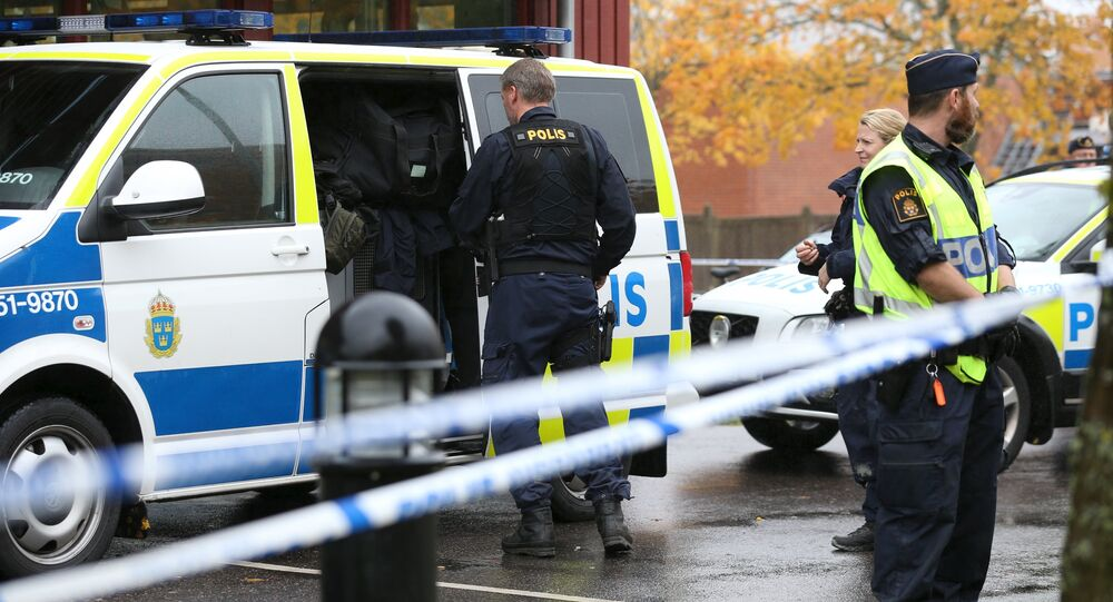 Police officers stand guard at a cordoned area after a masked man attacked people with a sword at a school in Trollhattan, western Sweden October 22, 2015