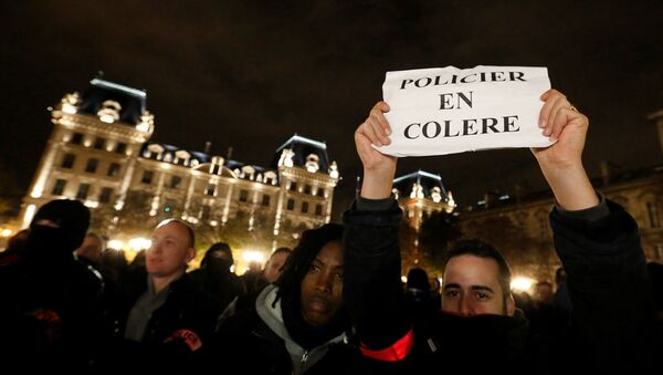 A policeman holds up a sign that reads, angry police as he joins other police officers in an unauthorised protest against anti-police violence in front of the Police Prefecture in Paris, France, October 21, 2016. - Sputnik France