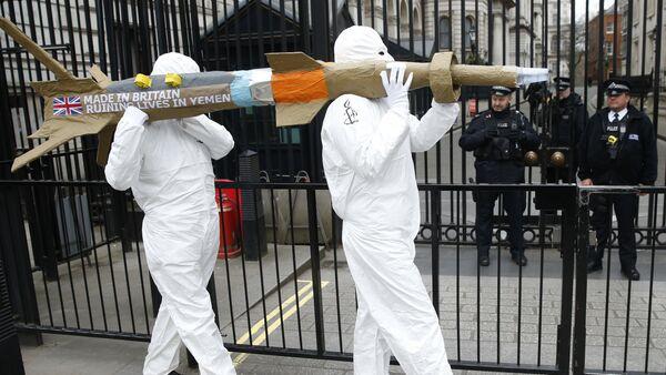 Les membres d'Amnesty International protestent en portant une maquette d'un missile contre la vente des armes par le gouvernement britannique d'armes à l'Arabie saoudite en dehors de Downing Street à Londres, vendredi le 18 mars 2016 - Sputnik France