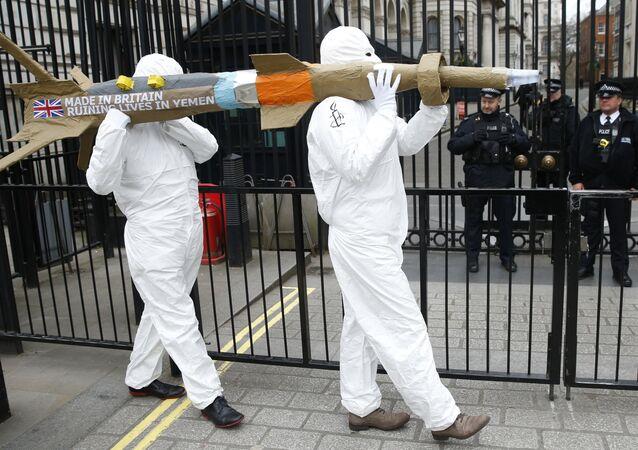 Les membres d'Amnesty International protestent en portant une maquette d'un missile contre la vente des armes par le gouvernement britannique d'armes à l'Arabie saoudite en dehors de Downing Street à Londres, vendredi le 18 mars 2016