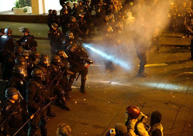 Un policier arrose la foule avec un irritant lors d'une manifestation contre l'élection du républicain Donald Trump comme président des États-Unis à Portland, Oregon, États-Unis le 12 Novembre 2016