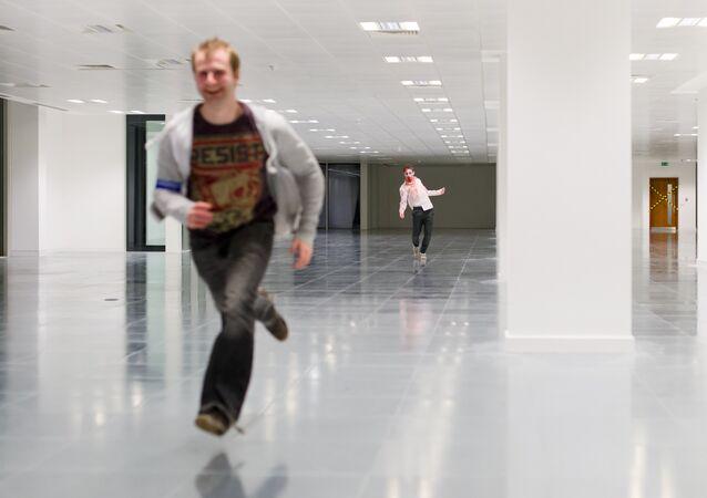 Un acteur zombie chasse un homme pendant un jeu de zombie