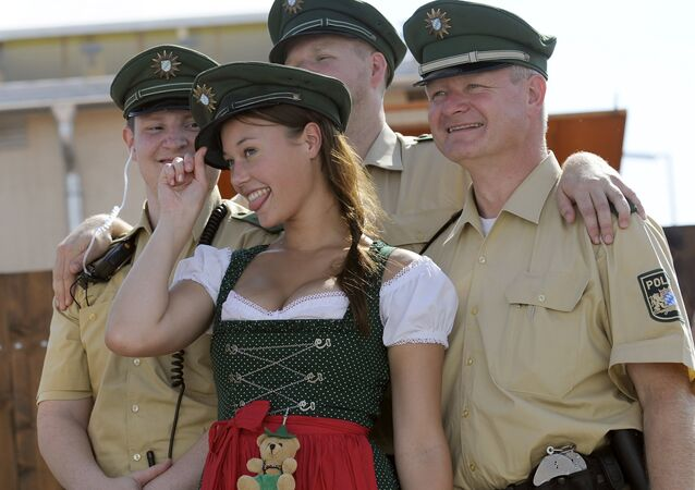 A young woman dressed with traditional Bavarian clothes wears a police hat as she poses with policemen at the start of the Oktoberfest beer festival