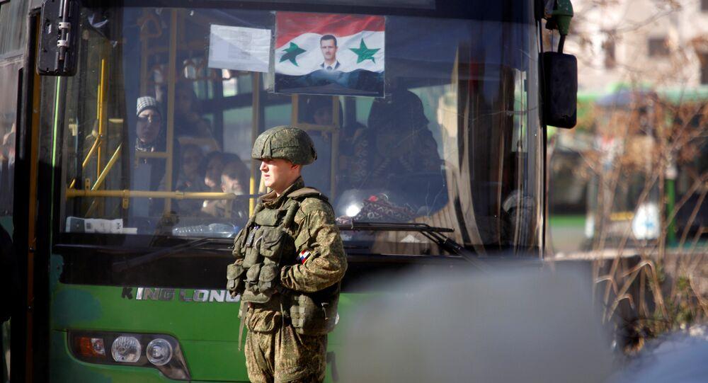 Un soldat russe à côté d'un bus qui a ramené des civils à Alep