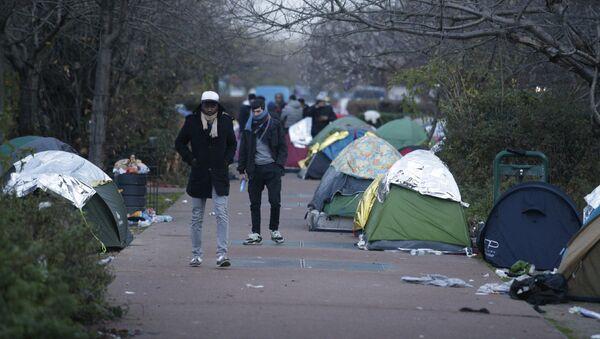 People walk by a makeshift camp set by migrants, on December 16, 2016 in Saint-Denis, a northern Paris' suburb. - Sputnik France