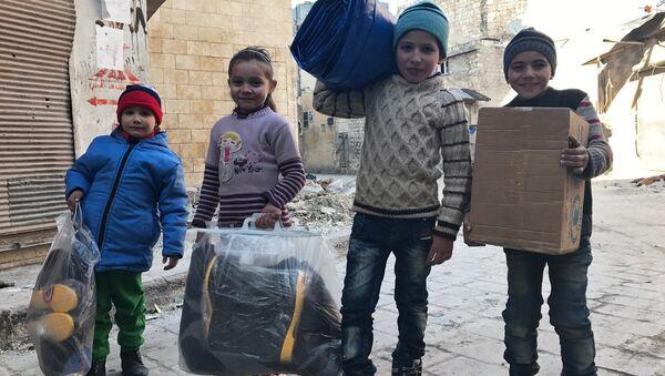 Дети, получившие первую гуманитарную помощь, в восточном квартале Алеппо. - Sputnik France