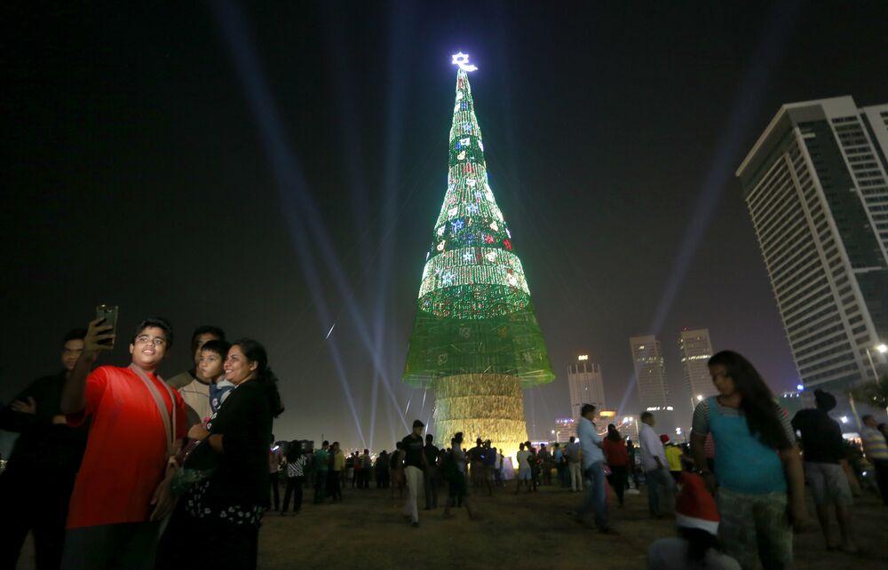 Une famille prend des photos devant un sapin de Noël à Colombo, au Sri Lanka