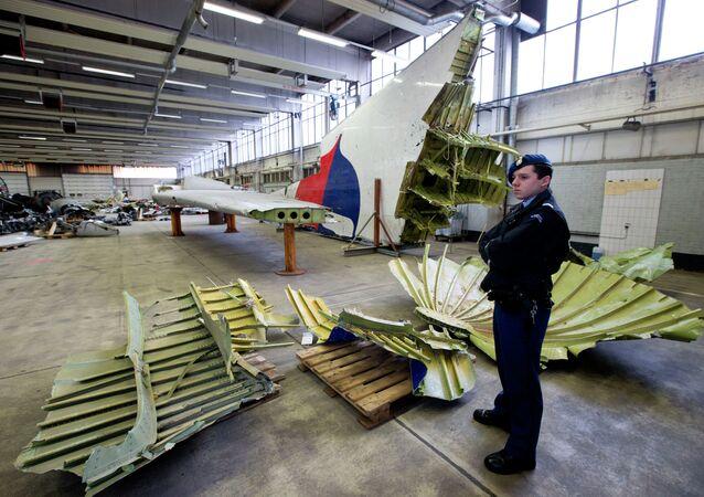 La police militaire néerlandaise à côté de fragments de l'avion du vol MH17 dans un hangar à la base aérienne de Gilze-Rijen, Pays-Bas, le 3 mars 2015