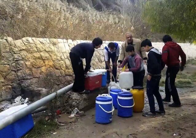 Des Syriens remplissent de l'eau.