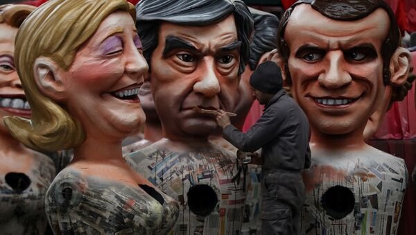 A man puts the final touche on a giant figure depicting right-wing presidential candidates Francois Fillon (C) next to others depicting far right presidential candidate Marine Le Pen (L) and centrist independent presidential candidate Emmanuel Macron, on January 27, 2017 in Nice, southeastern France, during the preparation of the 133rd Nice Carnival. - Sputnik France