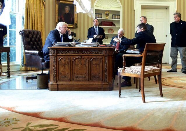 Le président américain Donald Trump (de gauche à droite), rejoint par le chef de cabinet Reince Priebus, le vice-président Mike Pence, le conseiller à la sécurité nationale Michael Flynn, le directeur des communications Sean Spicer et le conseiller principal Steve Bannon, s'entretient par téléphone avec le président russe Vladimir Poutine dans le bureau ovale de la Maison Blanche à Washington, aux États-Unis, le 28 janvier 2017
