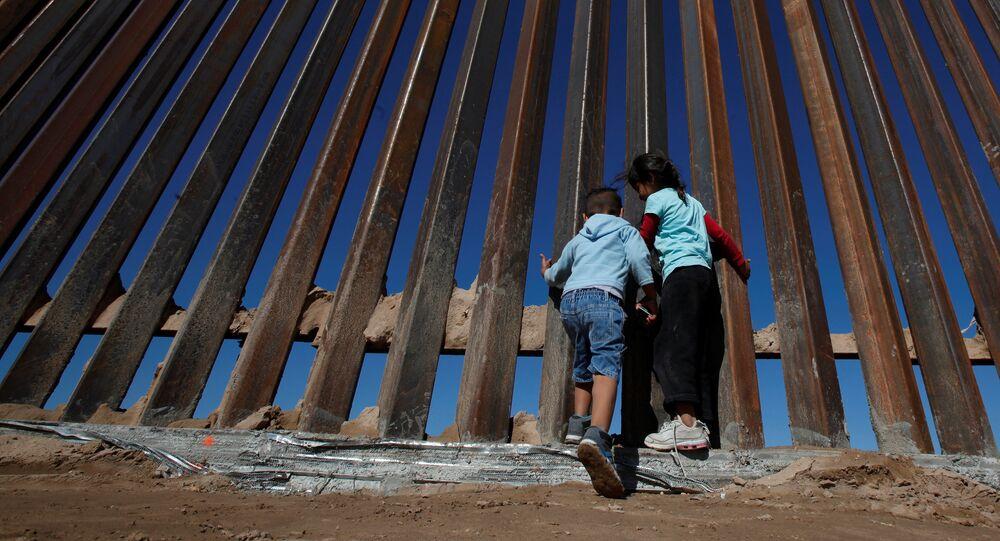 Les enfants jouent dans près d'une nouvelle section du mur frontalier entre les États-Unis et le Mexique à Sunland Park, aux États-Unis, le 18 novembre 2016