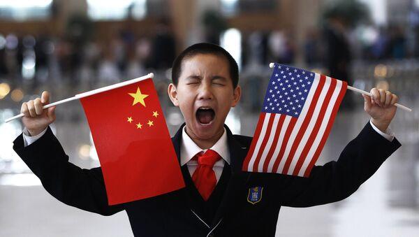 Un garçon tient des drapeaux chinois et américain à Pékin - Sputnik France