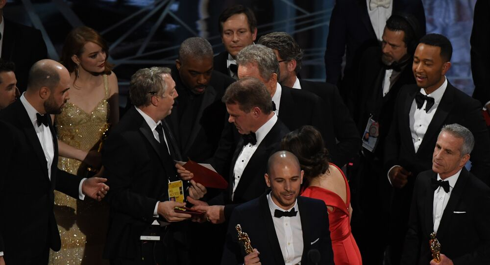 An Oscar show producer (3L) shows the winners card to the cast of La La Land after it mistakenly won the best picture instead of Moonlight at the 89th Oscars on February 26, 2017 in Hollywood, California.