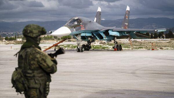 Un militaire russe devant un chasseur Soukhoï Su-34 sur la base aérienne de Hmeimim - Sputnik France