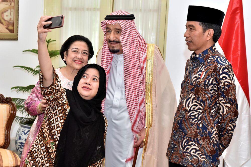 Le  président indonésien Joko Widodo regarde l'ex-présidente Megawati Sukarnoputri et sa fille la ministre Puan Maharani se faire photographier avec le roi d'Arabie saoudite Salman ben Abdelaziz Al Saoud en visite à Jakarta