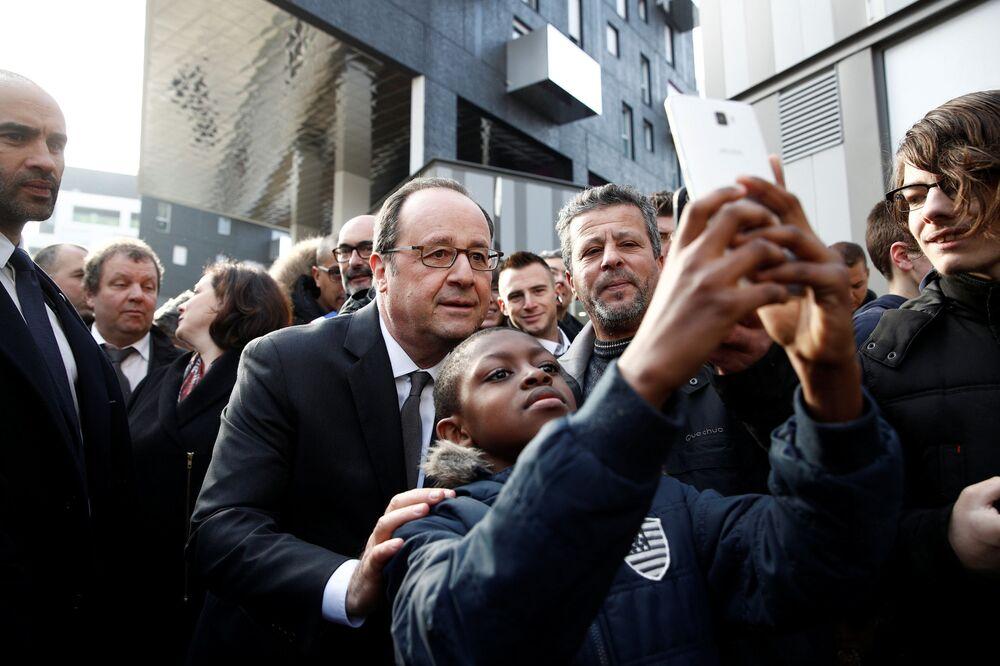 Le président français François Hollande se fait photographier avec un garçon dans la banlieue de Paris