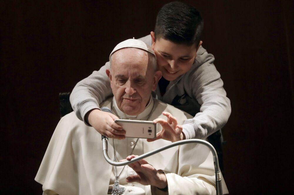 Le pape François, amateur de selfies, se fait photographier avec un garçon dans une église de Rome